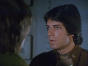 Zac (played by 70s Teen Hearthrob Rick Springfield).  You've been reduced from tragic first casualty in the Cylon Armageddon to mere plot point for sexual tension.